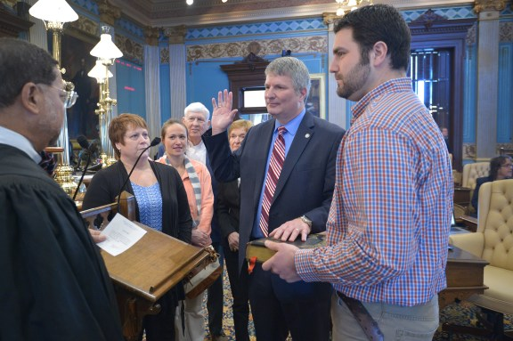 Michigan Supreme Court Chief Justice Robert P. Young (left) administers the oath of office to state Sen. Goeff Hansen, R-Hart (right), while Hansen's family members look on.