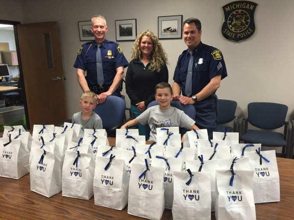 Michigan State Police Lt. Matt Kanitz, left, and Sgt. Charles Hockenson receive survival kits from Marnee Furman and her sons, Lincoln, 6, and Wyatt, 9.