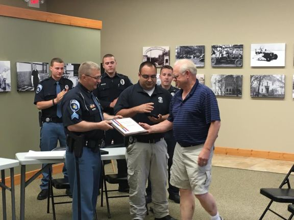 HPD Sgt. Kevin Skipski hands the award to Chief Leimback. Officer Juan Salazar is pictured in the middle, and officers Brian Hintz, Joshua Karafa and Alexander Schulz are pictured in the back row.