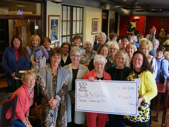 Barb Davidson is surrounded by Women Who Care members last June when the group selected the Wayne Elhart BE NICE Memorial Fund to receive their $100 personal contributions.