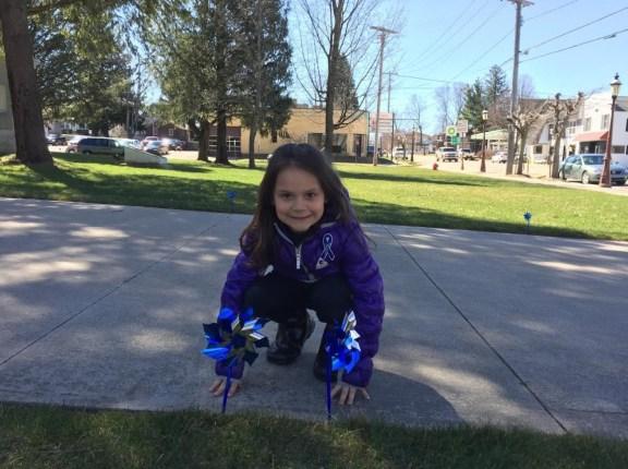 Selena Kosla, 6, places pinwheels near the courthouse entrance.