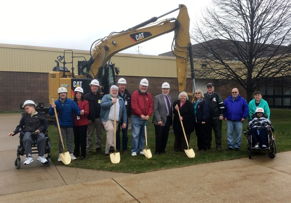 Students, administrators, teachers, board members, and construction team members pose in front of the building.