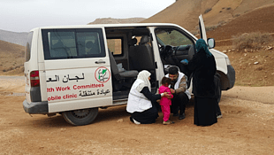 A doctor and nurse assistant with the Union of Health Work Committees providing assistance to a child the Al Maleh area. Credit: WHO/Alice Plate