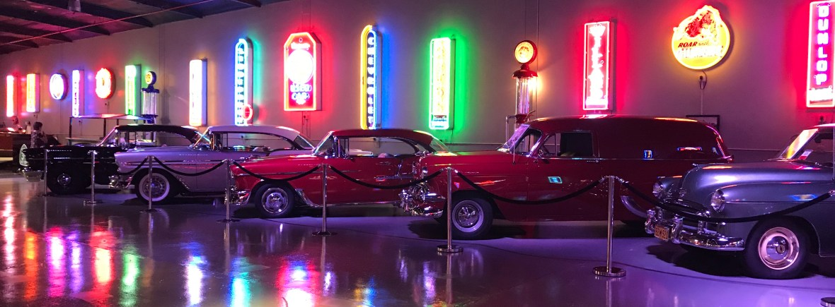 A neon-sign-lit view of some of the cars on display at Highway 39 Event Center