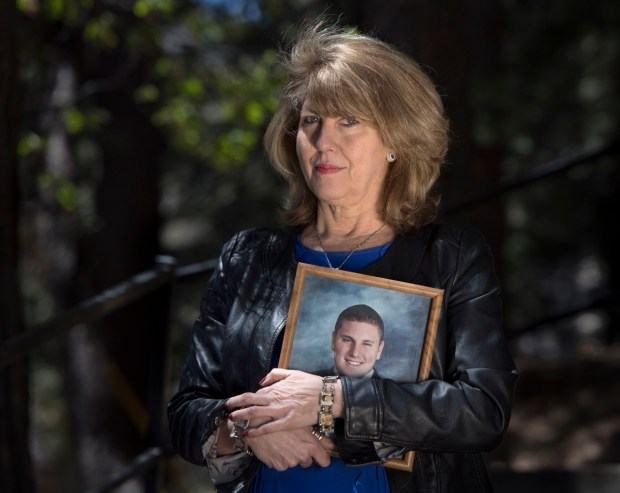 """Public Safety Advocate Wendy McEntyre founded the nonprofit Jarrod's Law after her son, Jarrod Autterson, died at age 23 of an overdose in a sober living home. She holds his high school graduation photo. """"The bottom line is nothing is going to stop me from taking down these rogue rehabs that are killing people...I've lost everything so there is really nothing anyone can take from me that will hurt me,"""" she said.(Photo by Mindy Schauer, Orange County Register/SCNG)"""