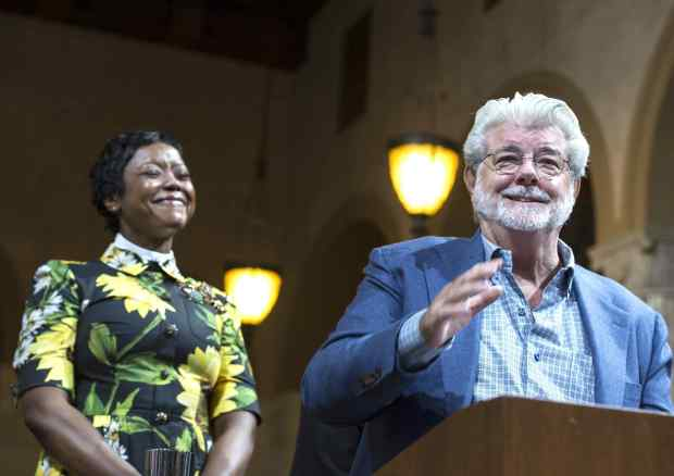 "George Lucas, right, filmmaker, creator of ""Star Wars,"" addresses the Los Angeles City Council members as his wife, Mellody Hobson, looks on during a meeting at City Hall in Los Angeles on Tuesday, June 27, 2017. Los Angeles City Council approved the Lucas Museum of Narrative Art project in Exposition Park. (Photo by Ed Crisostomo, Los Angeles Daily News/SCNG)"