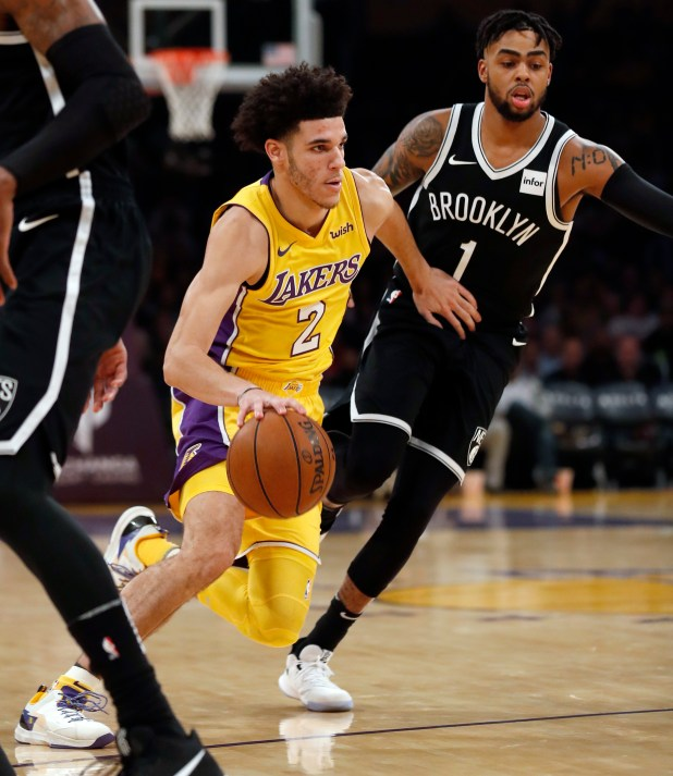 Los Angeles Lakers guard Lonzo Ball, left, dribbles to the basket past Brooklyn Nets guard D'Angelo Russell, right, during the first half of an NBA basketball game, Friday, Nov. 3, 2017, in Los Angeles. (AP Photo/Ryan Kang)
