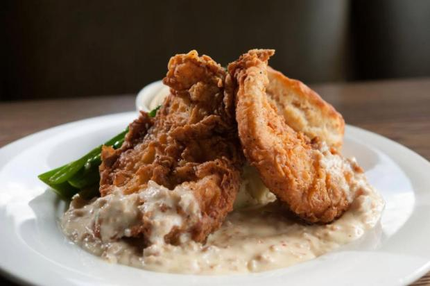 Rosemary's chicken and biscuits come home-battered and fried crisp with yukon mashed potatoes and sausage gravy along with a buttermilk biscuit with honey butter and grilled broccolini at Reunion Kitchen + Drink in Anaheim Hills. (File photo by Eugene Garcia)