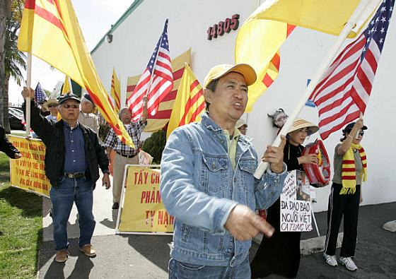 PROTEST: Trong Doan, center, leads a protest across the parking lot from Nguoi Viet Daily News in Westminster Tuesday to push for a public forum to air grievances regarding a photo that ran in the newspaper. The paper filed a lawsuit Feb 29 against three of the protesters.