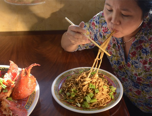 Owner Lan Thi Dao enjoys house noodles with Newport special spicy lobster at her Garden Grove restaurant, Tan Cang Newport Seafood. (File photo by Cindy Yamanka, Orange County Register/SCNG)