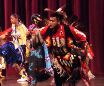 several young people dance in tribal clothing