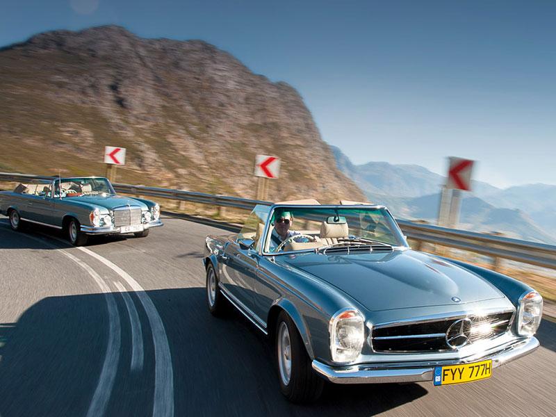 Zwei Mechatronik-Mercedes auf Kurvenfahrt: 280 SE (hinten) und 280 SL (vorne)