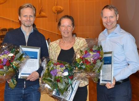 Bilde av de tre forskerne som mottok pris for fremragende forskning, oppstilt smilende med diplomer og blomster i hendene.