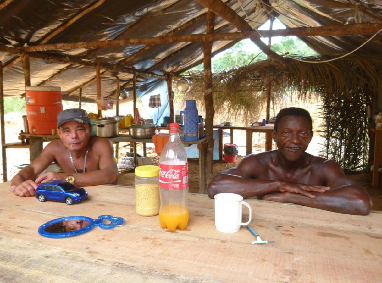 À esquerda, Domingo, e a seu lado, Eduardo, ambos dentro do acampamento, na parte em que fica a cozinha.