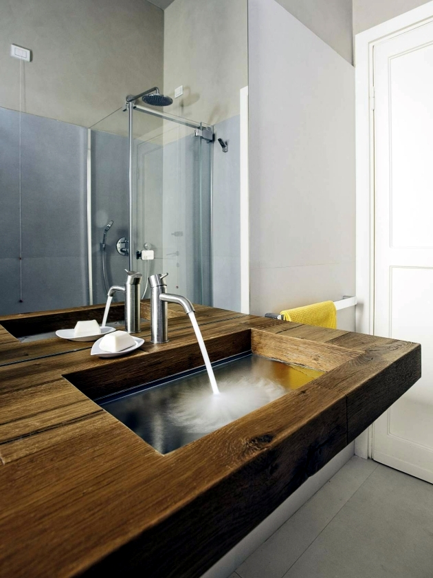 A wood vanity with glass basin of Lake creates illusions