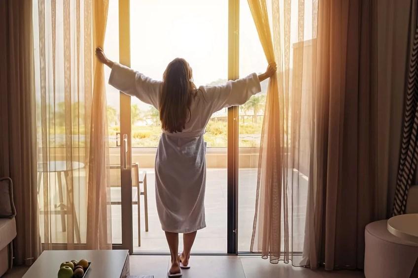 Femme en peignoir ouvrant des rideaux