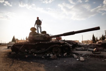 "Ein momentan wichtiges Thema für das EU INTCEN: der arabische Frühling. Fotobeschriftung: An armed fighter of the Free Syrian Army stands atop a destroyed Syrian army tank  to have his picture taken by a passer-by in the northern Syrian town of Azaz, some 47km north of Aleppo, on September 10, 2012, as UN envoy Lakhdar Brahimi admitted he faced a ""very difficult"" task in his bid to end the nearly 18-month conflict (Photo credit: SAM TARLING/AFP/GettyImages)."