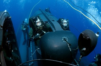 Members of SEAL Delivery Vehicle Team Two (SDVT-2) prepare to launch one of the team's SEAL Delivery Vehicles (SDV) from the back of the Los Angeles-class attack submarine USS Philadelphia (SSN 690) on a training exercise. The SDVs are used to carry Navy SEALs from a submerged submarine to enemy targets while staying underwater and undetected. SDVT-2 is stationed at Naval Amphibious Base Little Creek (Photo: Mate Andrew McKaskle, U.S. Navy).