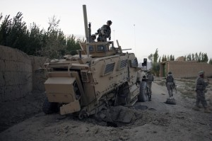 Soldiers from the U.S. Army's Alfa Company, 3rd brigade of 10th Mountain Division based in Fort Drum, New York, check damage to their armored vehicle after an IED (improvised explosive device) laid by the Taliban exploded along the road near the village of Eber in Logar province September 26, 2009. No one was injured in the incident.
