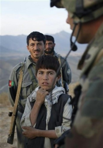 A young Afghan boy, who was in a car stopped at a joined NATO, Afghan National Army and police checkpoint, listens to the Foreign Legion officer near the Rocco combat outpost in the Surobi disctrict, some 50 kms north-east of Kabul, Afghanistan, in November 2009.