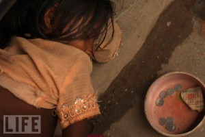 A girl sleeps beside a begging bowl on the ground at a rice market on July 17, 2008 in Dhaka, Bangladesh.