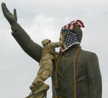 A US Marine covers the face of Iraqi President Saddam Hussein's statue with the US flag in Baghdad's al-Fardous square 09 April 2003 (Photo: Ramzi Haidar / AFP / Getty Images).