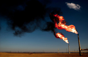 """A natural gas """"flare off,"""" too expensive to utilize, colors the Sahara Desert's twilight sky."""