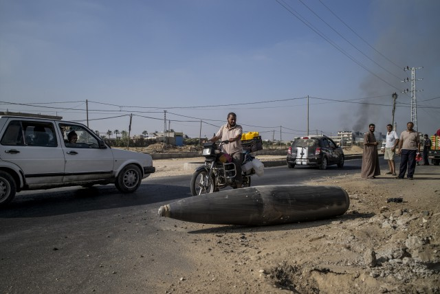 Palestinian onlookers and motorists pause to inspect an Israeli army bomb laying unexploded on the road that links northern and southern Gaza, in Deir al-Balah, in the central Gaza Strip, on August 1, 2014 (Photo: Marco Longari / AFP).