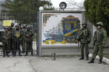 Ukrainian soldiers, left and unidentified gunmen, right, guard the gate of an infantry base in Privolnoye, Ukraine, Sunday, March 2, 2014. Hundreds of unidentified gunmen arrived outside Ukraine's infantry base in Privolnoye in its Crimea region. The convoy includes at least 13 troop vehicles each containing 30 soldiers and four armored vehicles with mounted machine guns. The vehicles — which have Russian license plates — have surrounded the base and are blocking Ukrainian soldiers from entering or leaving it. (Darko Vojinovic/AP)