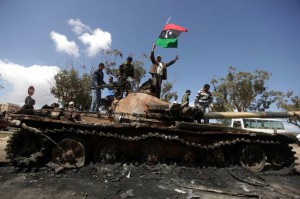 Libyan rebels wave their flag on top of a wrecked tank belonging to Moammer Khaddafi's forces on the western entrance of Benghazi on March 20, 2011.