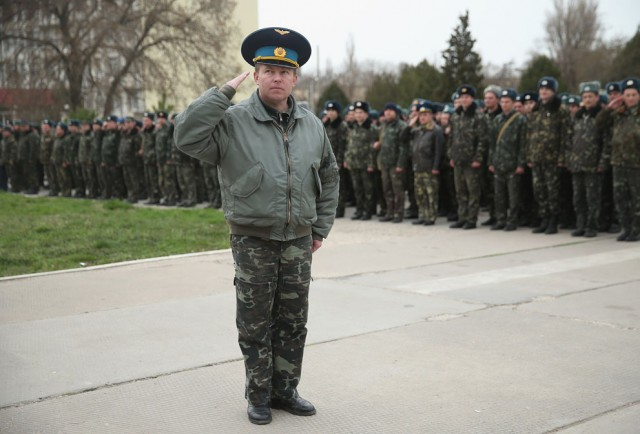 Colonel Yuliy Mamchur, commander of the Ukrainian military garrison at Belbek airbase, salutes before leading over 100 of his unarmed troops to retake Belbek airfield from soldiers under Russian command in Crimea, on March 4, 2014 in Lubimovka, Ukraine. After spending a tense night anticipating a Russian attack following the expiration of a Russian deadline to surrender, in which family members of troops spent the night at the garrison gate in support of the soldiers, Mamchor announced his bold plan to his soldiers early that morning (Photo: Sean Gallup / Getty Images).