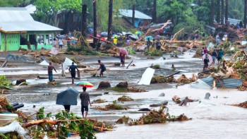People walk through debris resulting from days of heavy rain in the Solomon Islands, which caused flash flooding and the Mataniko River in Honiara to burst its banks, April 4, 2014 (Photo: Tony Bransby).