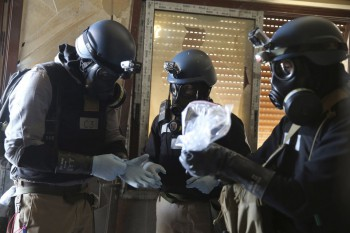 A U.N. chemical weapons expert, wearing a gas mask, holds a plastic bag containing samples from one of the sites of an alleged chemical weapons attack in the Ain Tarma neighbourhood of Damascus August 29, 2013 (Photo: Mohamed Abdullah / Reuters)