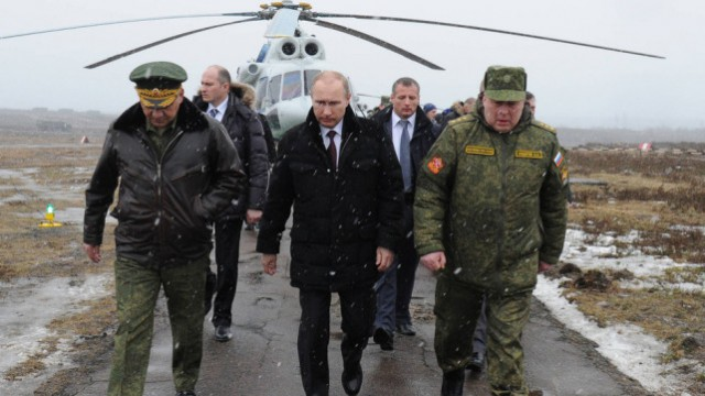 Russian Federation President Vladimir Putin (center) with Russian Federation Defense Minister and General of the Army Sergei Shoigu (left) and the commander of the Western Military District Colonel General Anatoly Sidorov (right).
