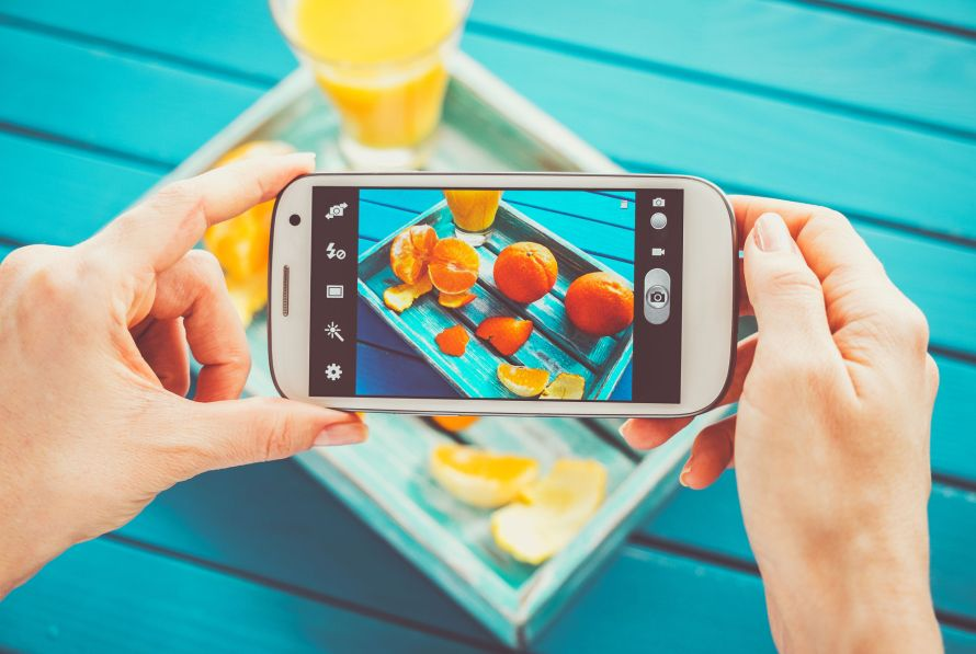 39194515 - woman taking picture of vintage tray with fruits on her smartphone. top view