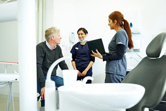 A dentist talks with two staff members in a dental office.