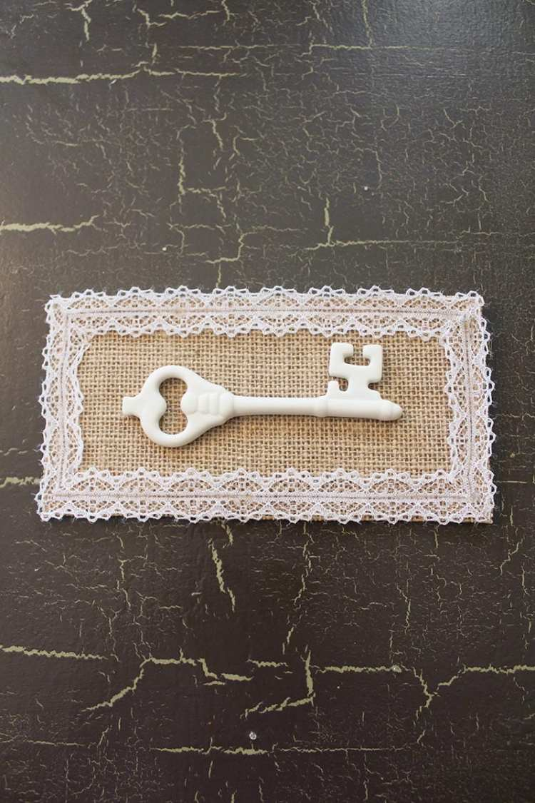 Key Artwork | A white porcelain key, burlap backing and lace all come together in this vintage-inspired mounted key artwork. A super easy DIY for a super cute decor item!