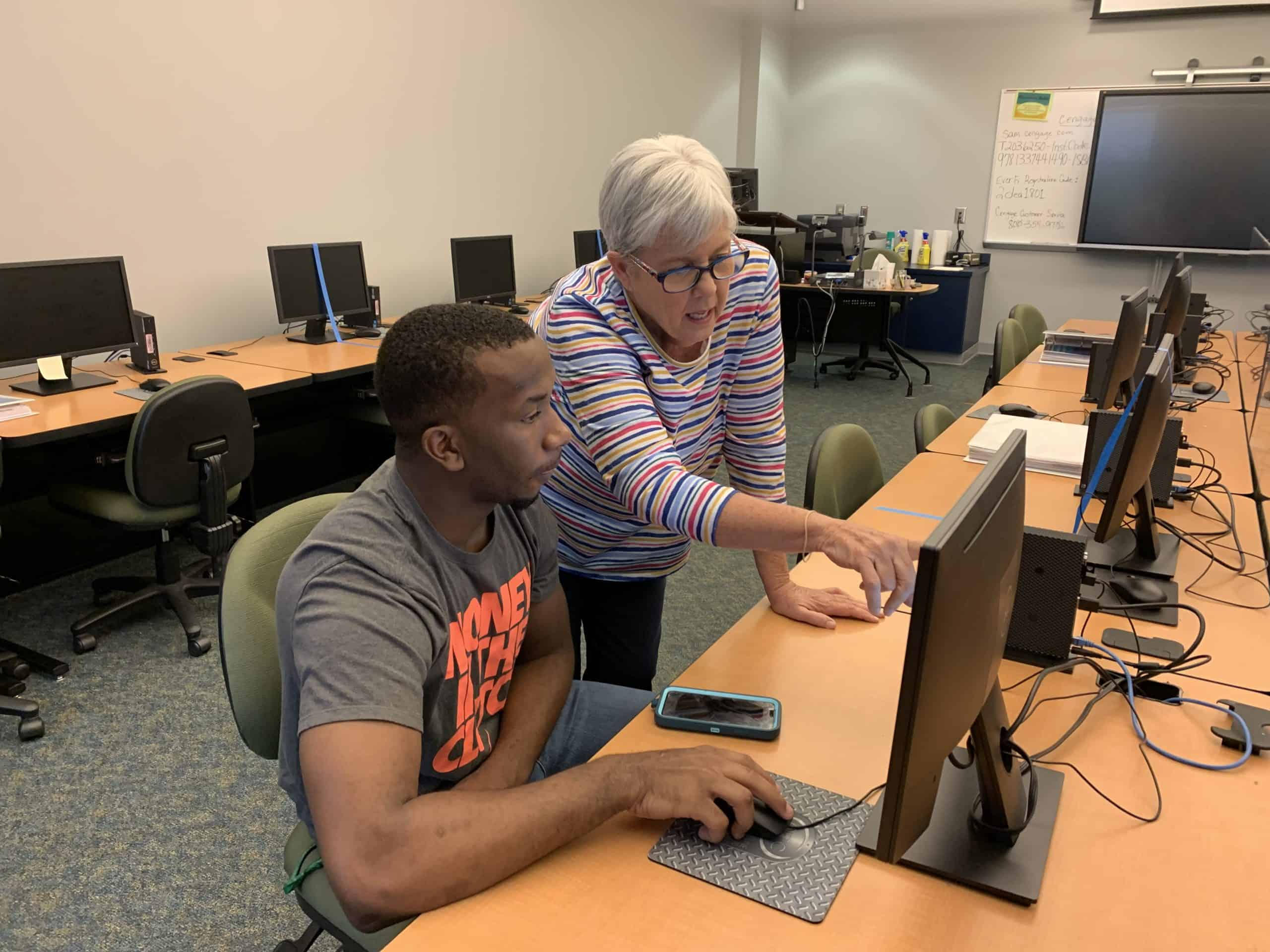 OFTC student in the tutoring lab at a computer receiving some instruction