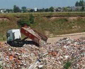 Un camion che scarica inerti in una discarica di inerti
