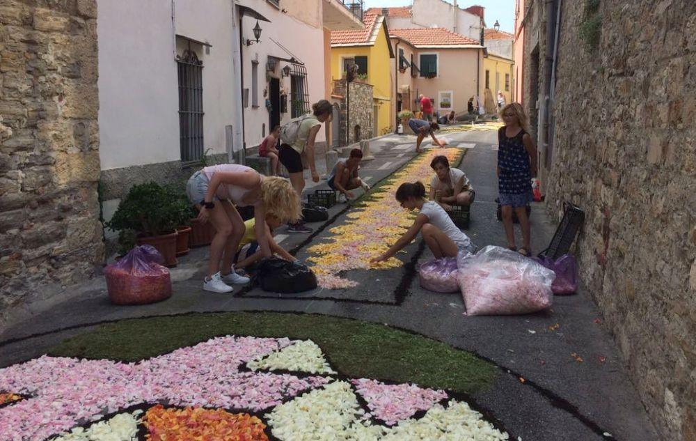 Le immagini di alcuni volontari che hanno lavorato duramente per preparare l'infiorata a Diano Castello