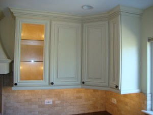 Photo displays Antique White wall cabinets presenting glass shelving, crown moulding and installed nobs to doors. These are available by coming to our showrooms, 28873 Lorain Rd North Olmsted Ohio 44070 Phone: 440-772-4039 and 35742 Vine Street Eastlake Ohio 44095 440 525 5135