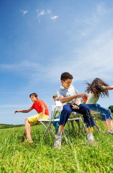 Kids playing game musical chairs and sitting fast on chairs in circle outside in summer