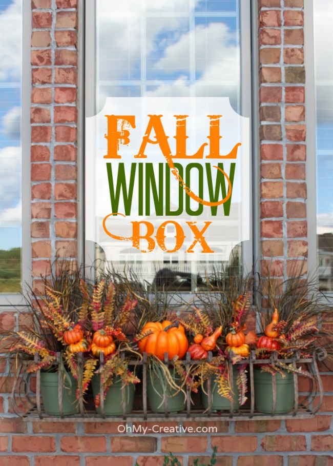 fall window box with pumpkins and fall silk greens