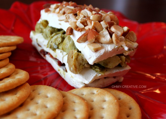This Layered Sun-dried Tomato and Artichoke Spread Appetizer is easy to make, tasty and perfect for any occasion. The red and green layers make it especially pretty for the holidays!   OHMY-CREATIVE.COM #artichokeappetizer #creamcheeseappetizer #layeredsundriedtomatoartichokespread #artichokespread #pesto