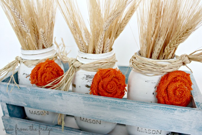 This Easy Fall DIY Centerpiece is a perfect Fall decor accent for the home. OHMY-CREATIVE.COM | Fall Decor | Mason Jar Centerpiece | Fall Mason Jar Craft | Fall Decorating | Painted Mason Jars | How to make a rosette | Wheat Fall decor | How to decorate for Fall | Crate Decor | Fall Mason Jar Decor | Fall Home Decor | Mason Jar Centerpieces