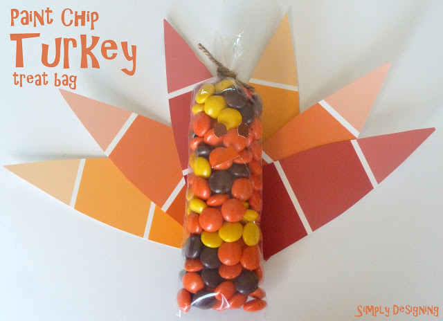 paint chip turkey treat bag are filled with autumn candies and fall colored paint chips make it tail.