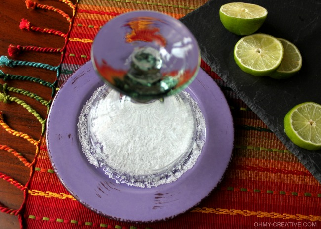 margarita glass on a purple plate with salt.