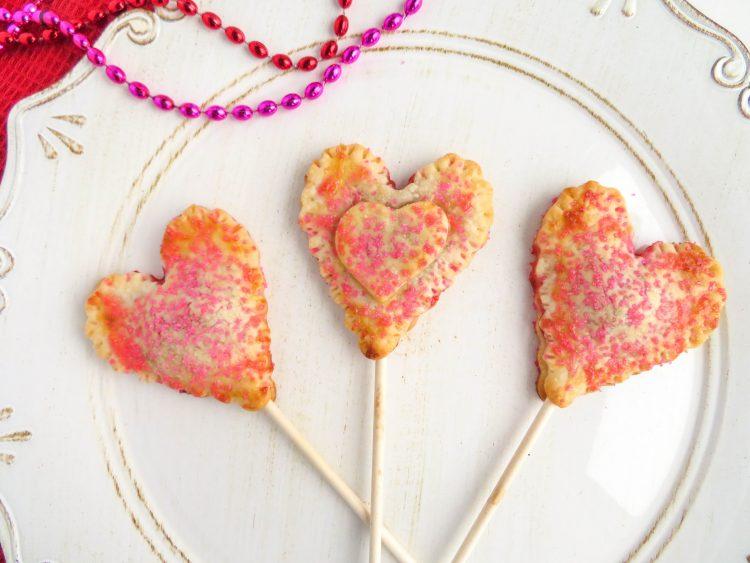 Mini Cherry Pies - Heart Pie Pops - A sweet Valentine's Day Treat! OHMY-CREATIVE.COM | Heart Shaped | Valentine's Day Dessert | Pie Pops | Pie Crust | Cherry Pie | Pillsbury Pie Crust | Premade Pie Crust | Sprinkles | Handheld pies | Mini Pies | Heart