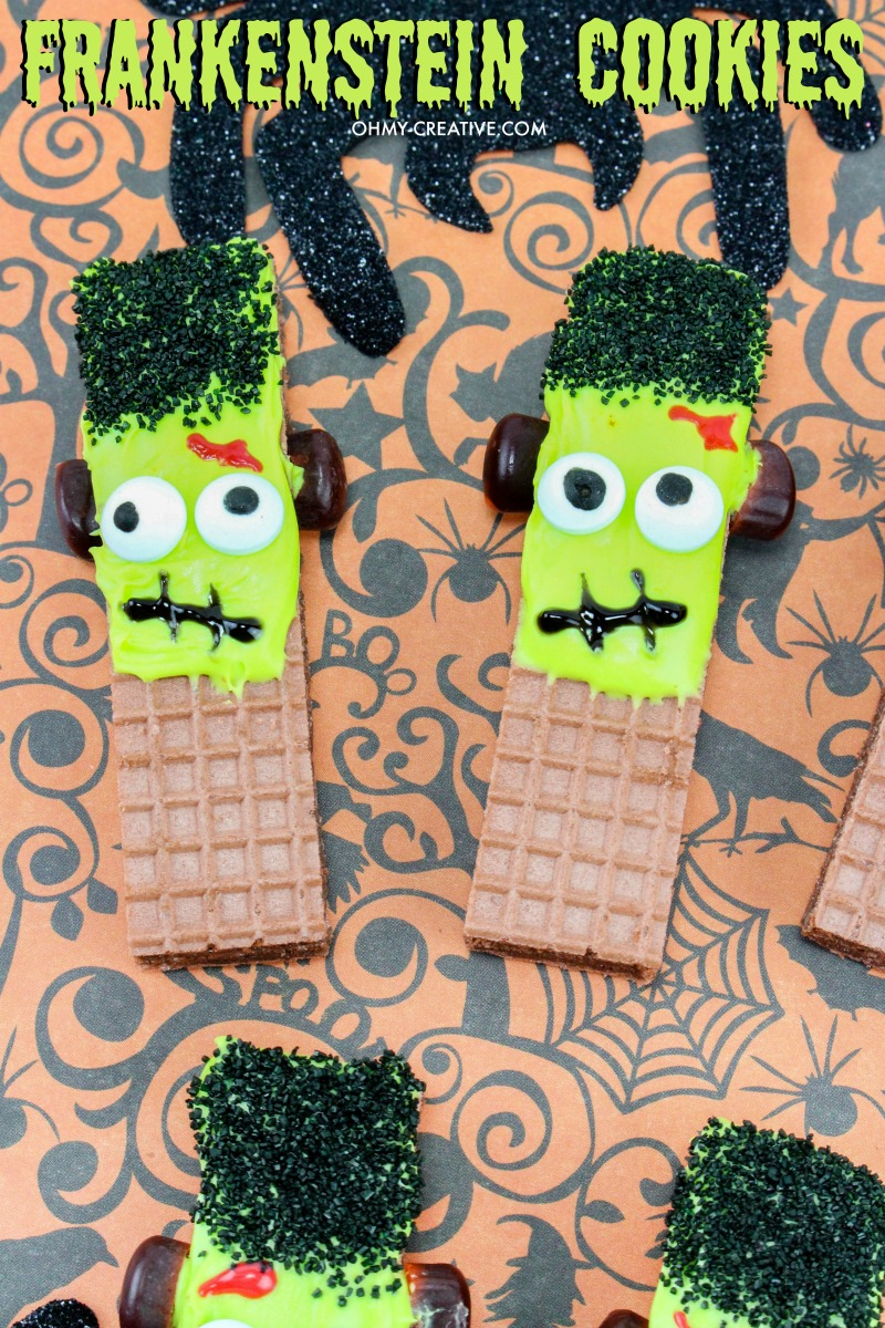 Frankenstein Cookies For Halloween made from store bought wafer cookies on a Halloween paper backdrop