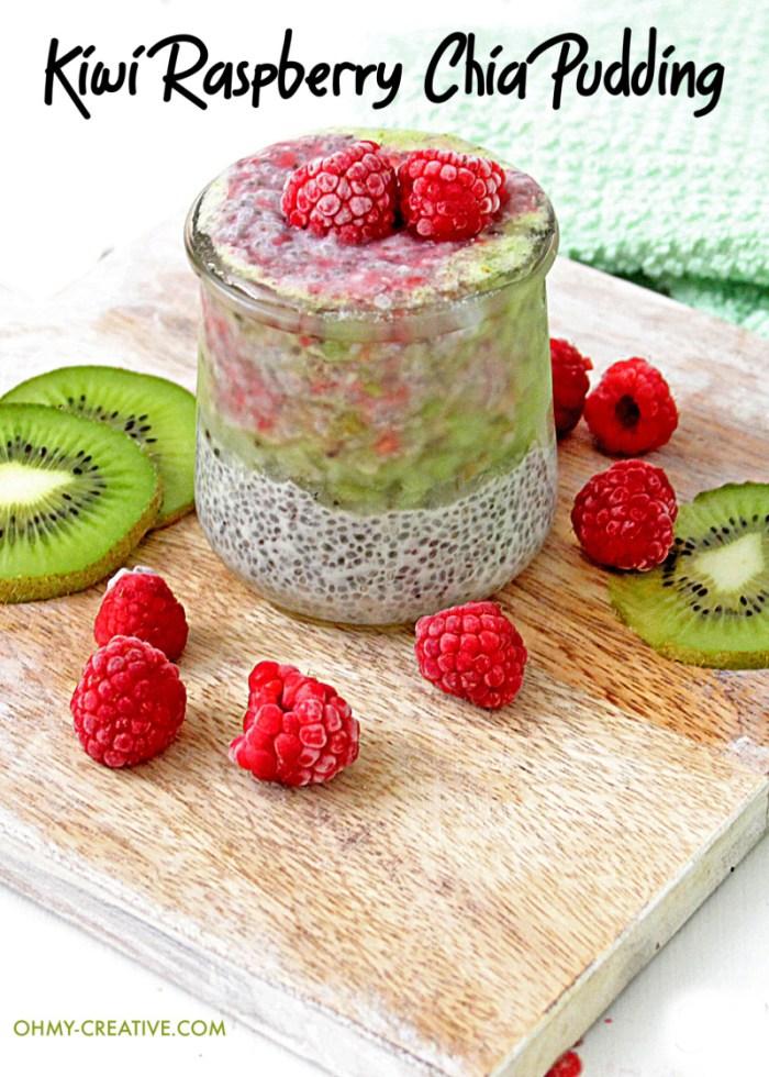 Kiwi Raspberry Chia Pudding on a cutting board with sliced kiwi and raspberries